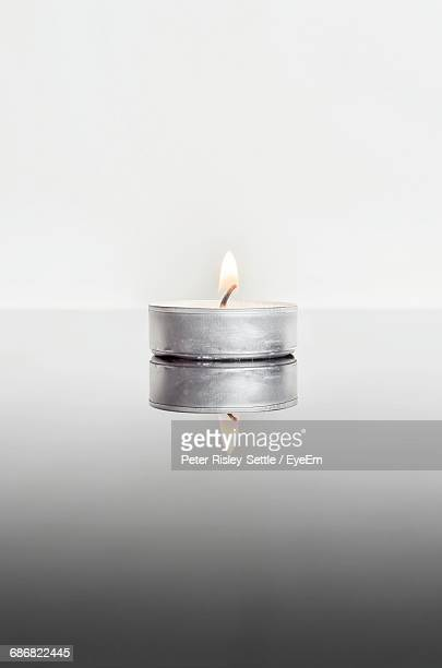 Reflection Of Lit Tea Light Candle On Table Against White Background
