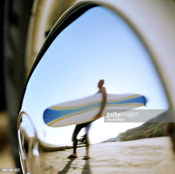 Reflection of man carrying surfboard in hub cap of car wheel