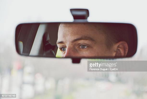 Reflection Of Man In Car On Rear-View Mirror