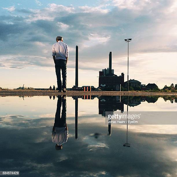 Reflection Of Man In Puddle Against Sky