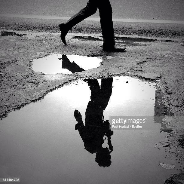reflection of man in puddle while walking roadside - charco fotografías e imágenes de stock