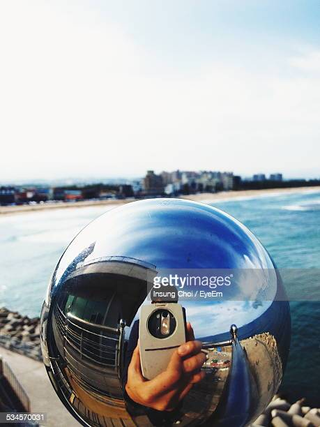 Reflection Of Man On Metallic Ball Photographing Lake Against Sky