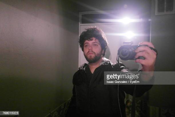 Reflection Of Man On Mirror While Photographing Using Camera