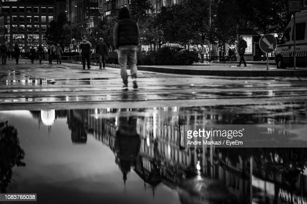 Reflection Of Man On Puddle In City During Sunset
