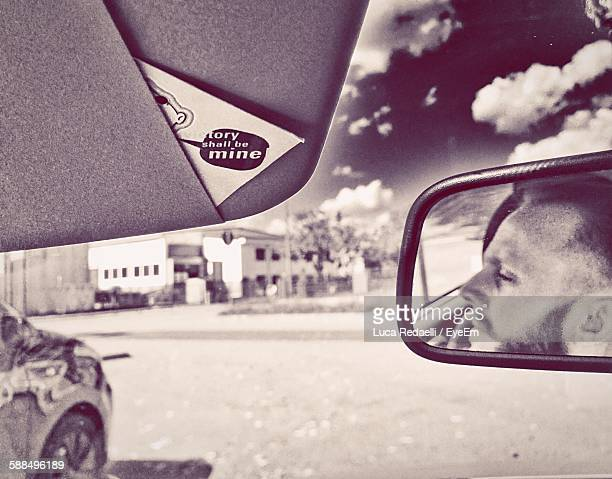 Reflection Of Man On Rear-View Mirror Against Sky