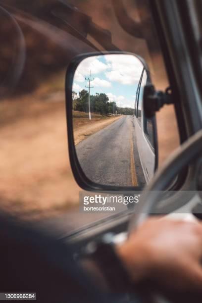 reflection of man on side-view mirror - bortes foto e immagini stock