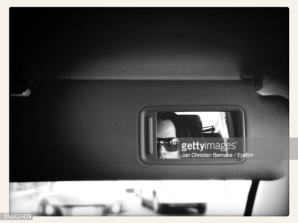 Reflection of man on visor mirror in car