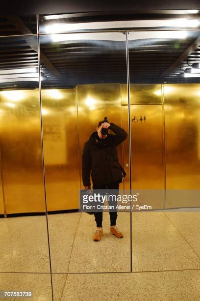 reflection of man photographing on mirror in restroom - cristian neri foto e immagini stock