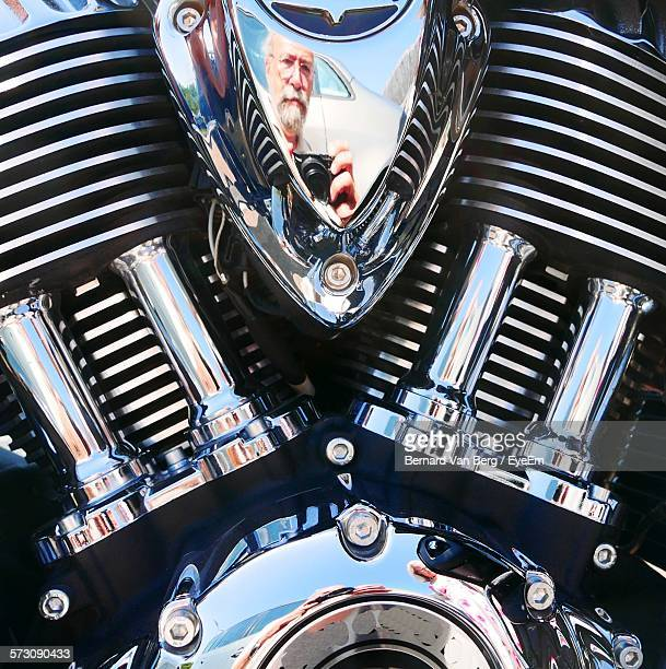 Reflection Of Man Photographing On Motorcycle Engine