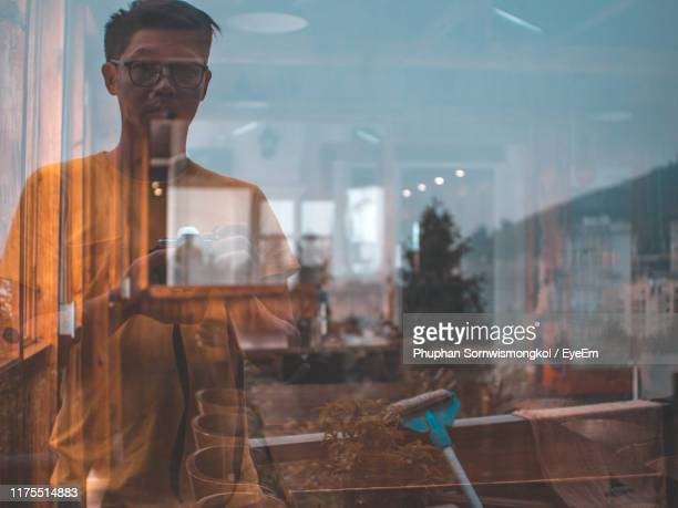 reflection of man photographing on store window - store window stock pictures, royalty-free photos & images
