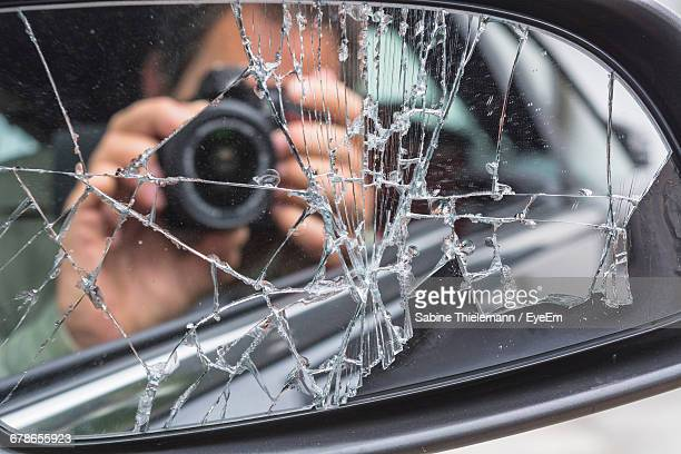 Reflection Of Man Photographing Through Camera On Broken Side-View Mirror