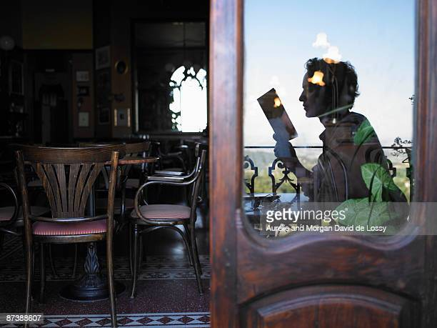 Reflection of man reading in cafe.