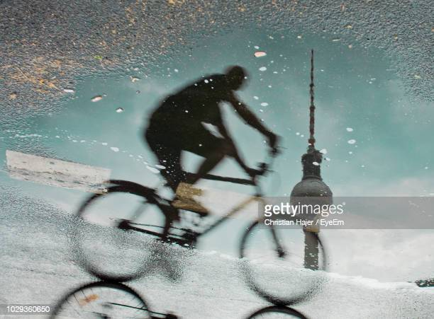 reflection of man riding bicycle with fernsehturm in puddle on street - central berlin stock pictures, royalty-free photos & images