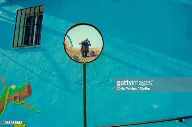 Reflection Of Man Seen In Mirror Against Wall