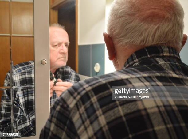 Reflection Of Man Shaving On Mirror In Bathroom At Home