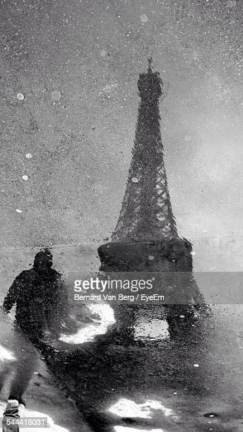Reflection Of Man Standing By Eiffel Tower Against Sky On Puddle