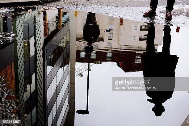 Reflection Of Man Standing On Street By Buildings In Puddle