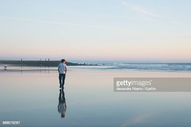 Reflection Of Man Walking At Beach Against Sky During Sunset