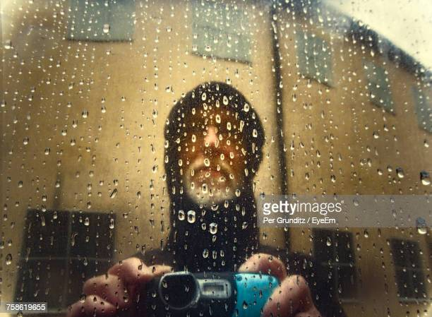 Reflection Of Man With Camera On Metallic Surface During Rainy Season