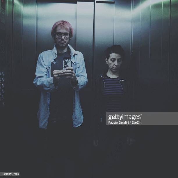 Reflection Of Man With Friend Photographing In Elevator On Mirror