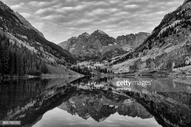 reflection of maroon peak and north maroon peak in maroon lake at maroon bells scenic area - aspen colorado stock photos and pictures