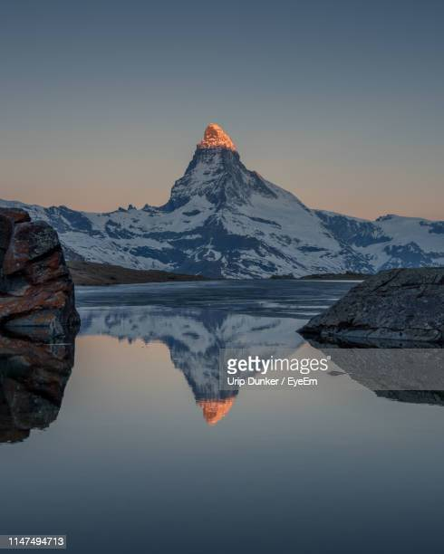 reflection of matterhorn mountain in lake against clear sky during sunset - zermatt stock pictures, royalty-free photos & images
