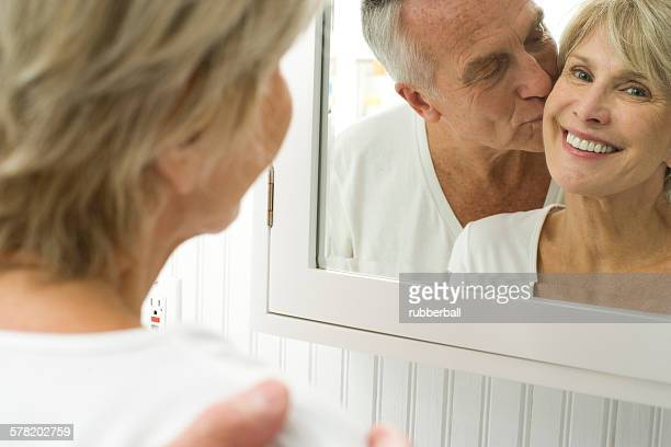 reflection of mature couple kissing in mirror - couple and kiss and bathroom stock photos and pictures