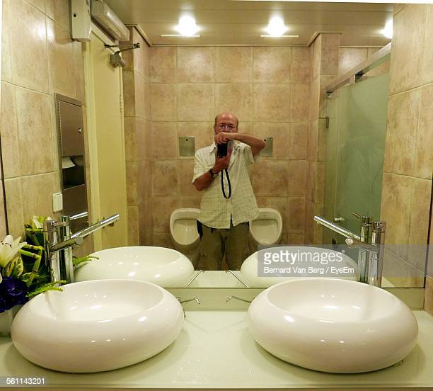 Reflection Of Mature Man In Bathroom Mirror Taking Selfie