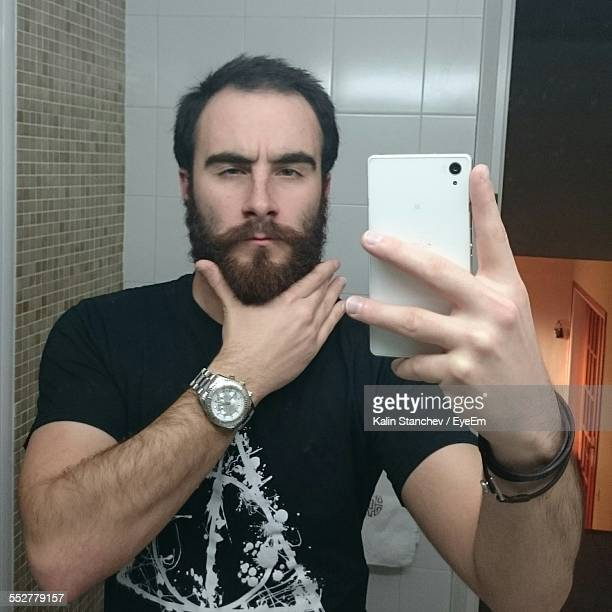 reflection of mid adult man taking selfie in front of mirror at home - mirror selfie stock pictures, royalty-free photos & images