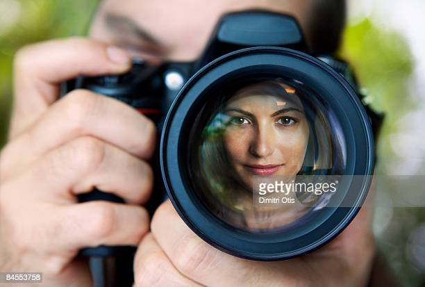 Reflection of model in photographer's lens
