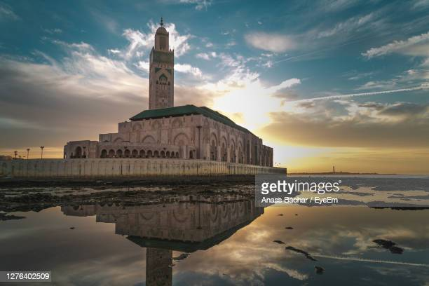 reflection of mosque by sea during sunset - casablanca morocco stock pictures, royalty-free photos & images