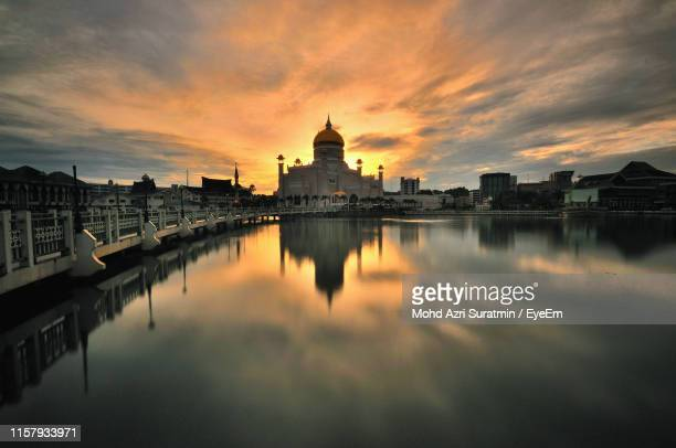 reflection of mosque in river against sky during sunset - bandar seri begawan stock photos and pictures