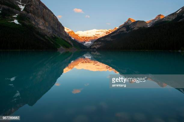 reflection of mount victoria in lake louise at sunrise - lake louise stock photos and pictures