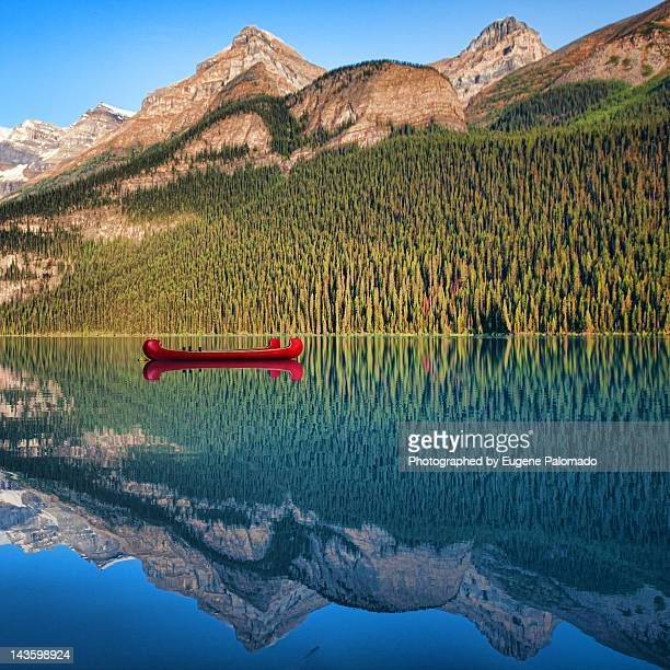 Reflection of mountain and boat in lake
