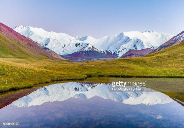 reflection of mountain range in lake - kyrgyzstan stock pictures, royalty-free photos & images