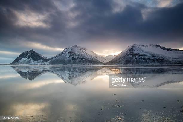 reflection of mountains on ocean at sunset in vatnajokull national park in eastern iceland. - alex saberi fotografías e imágenes de stock