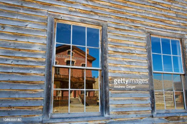 Reflection of old abandoned brick hotel in ghost town of Bannack, MT in window of faded paint wall.