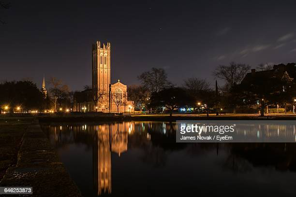 reflection of old church on calm lake against sky at night - norfolk virginia stock photos and pictures