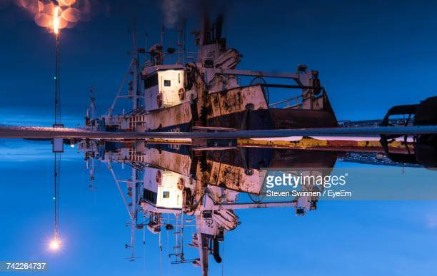 Reflection Of Old Ship In Sea Moored At Harbor During Night
