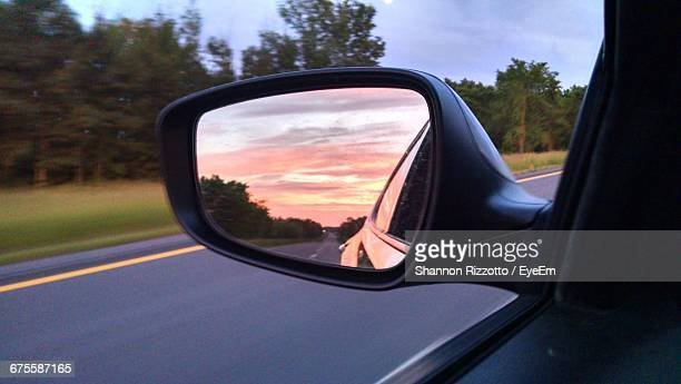 Reflection Of Orange Sky On Side-View Mirror During Sunset