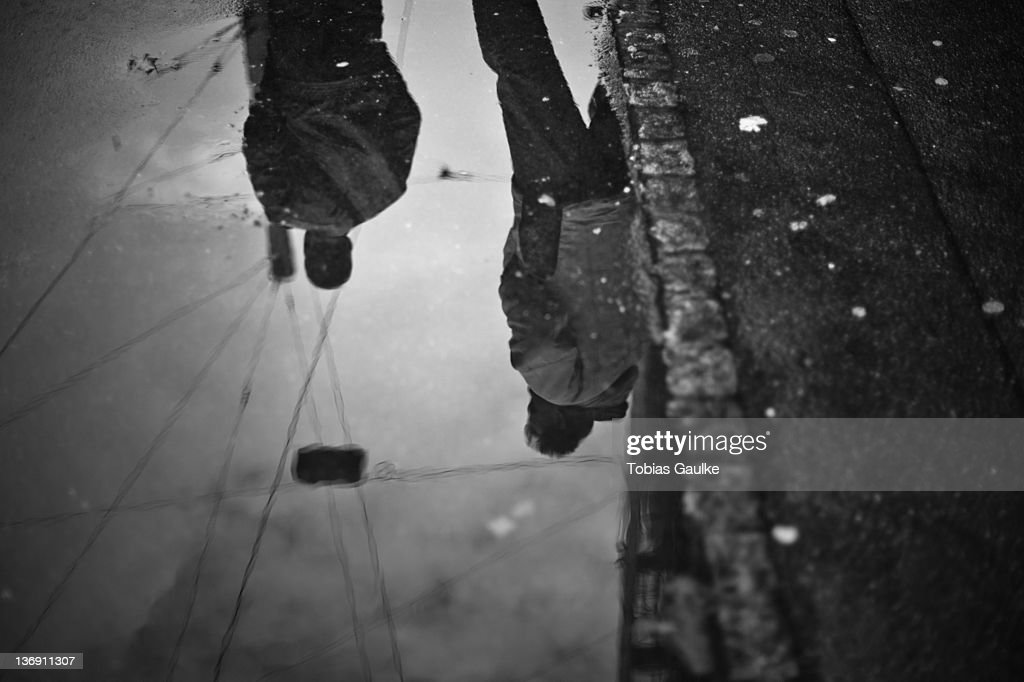 Reflection of people in puddle : Stock-Foto