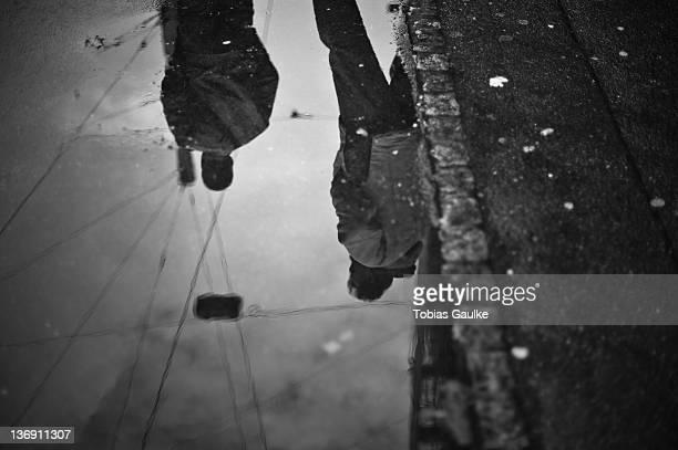 reflection of people in puddle - tobias gaulke stock-fotos und bilder