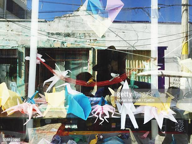 reflection of people on glass window of shop - isla mujeres stock photos and pictures