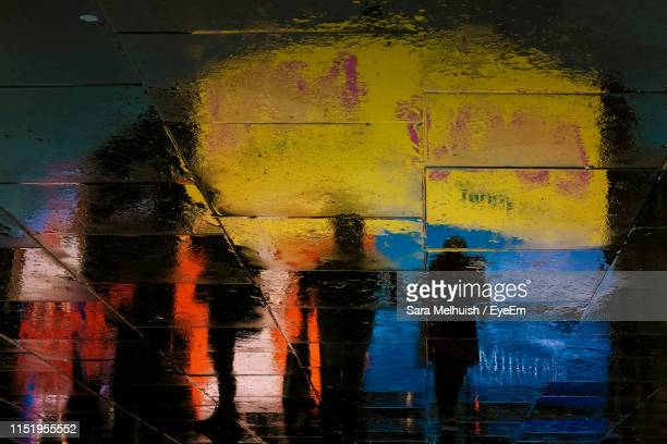 reflection of people on wet footpath in city at night - small group of people stock pictures, royalty-free photos & images