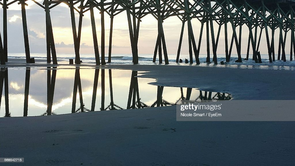 Reflection Of Pier In Sea Against Sky At Sunset : Stock Photo