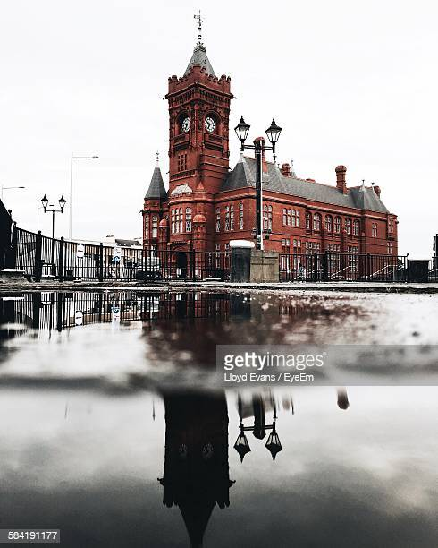 Reflection Of Pierhead Building In Puddle