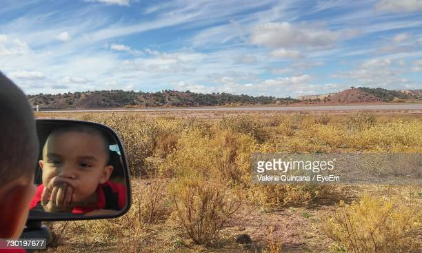 Reflection Of Playful Boy On Side-View Mirror Against Field