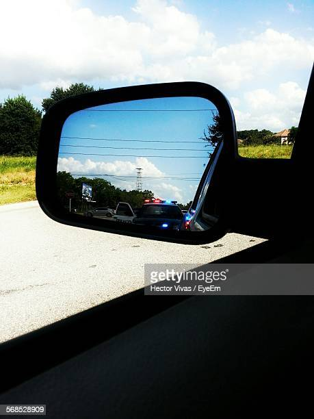 Reflection Of Police Car On Side-View Mirror Against Sky