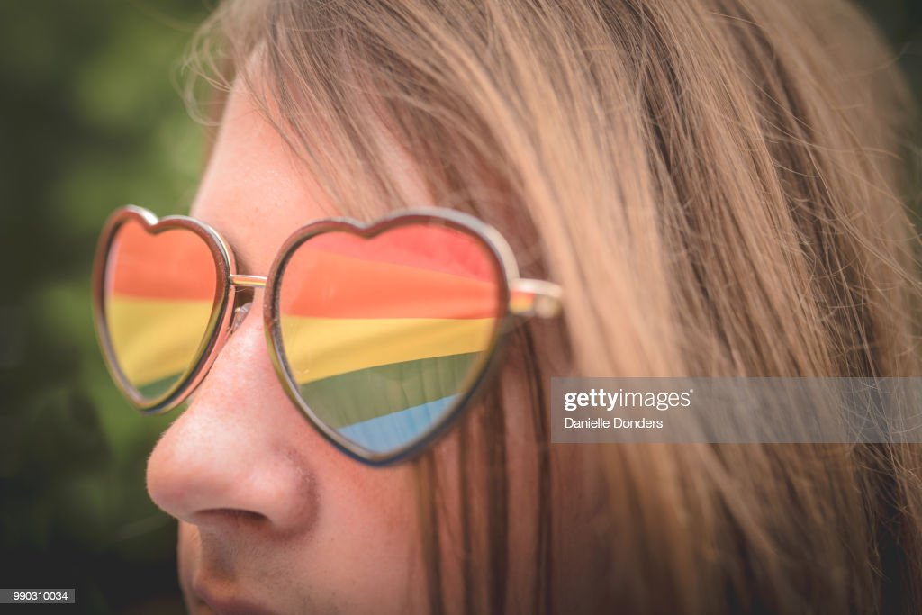 Reflection of rainbow pride flag in young person's heart-shaped glasses : Foto de stock