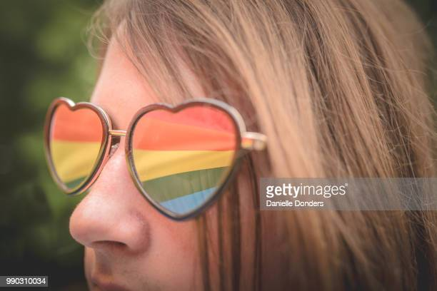 Reflection of rainbow pride flag in young person's heart-shaped glasses
